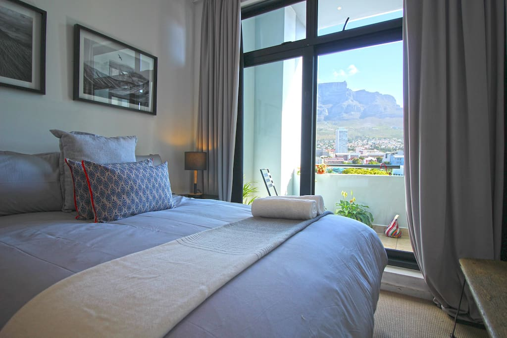 Spacious bedroom with comfortable queen bed, opening to balcony with views of Table Mountain