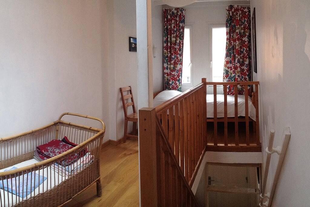L'étage avec un lit une place et un berceau