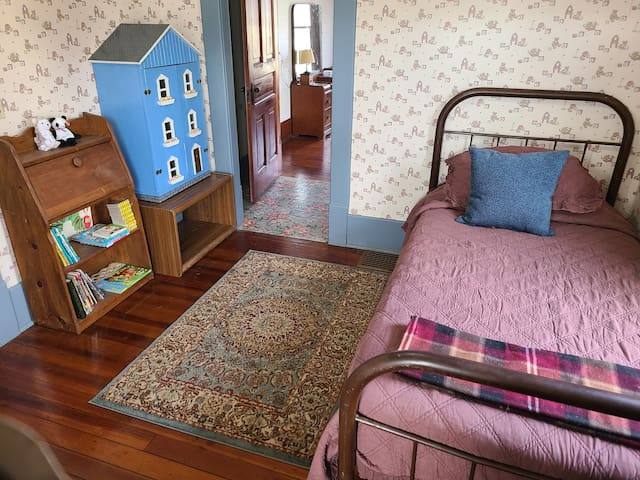 Bedroom 2 has two twin beds, along with kid's books, more toys, and a dollhouse!