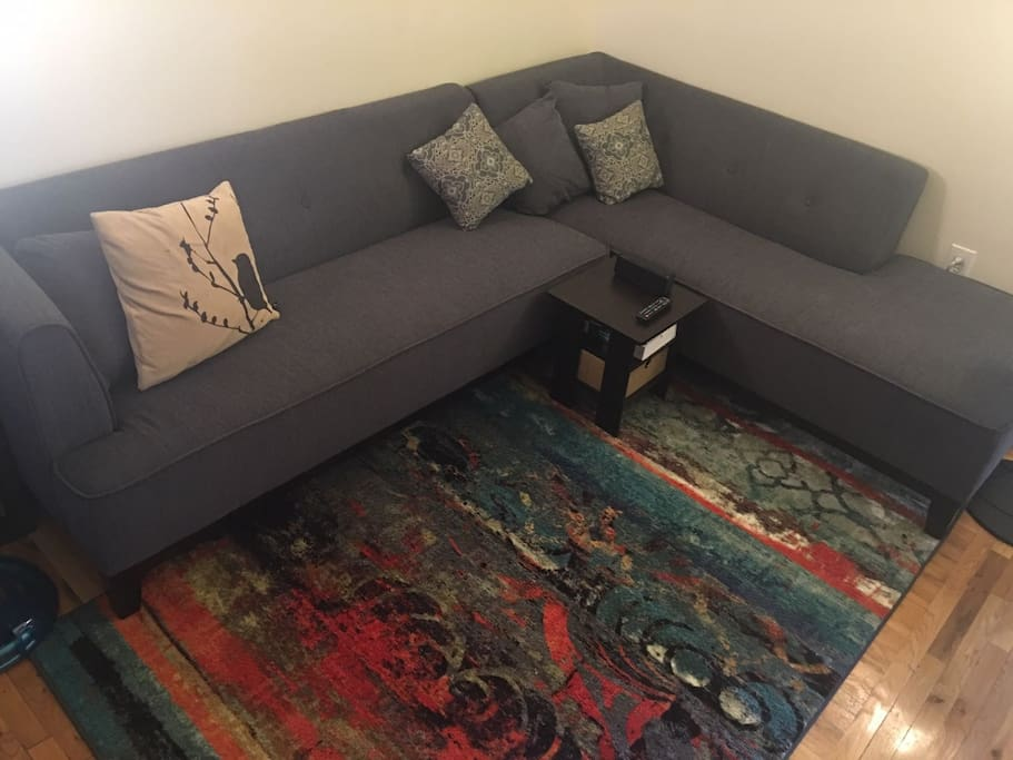 Spacious living room with large sectional and TV.