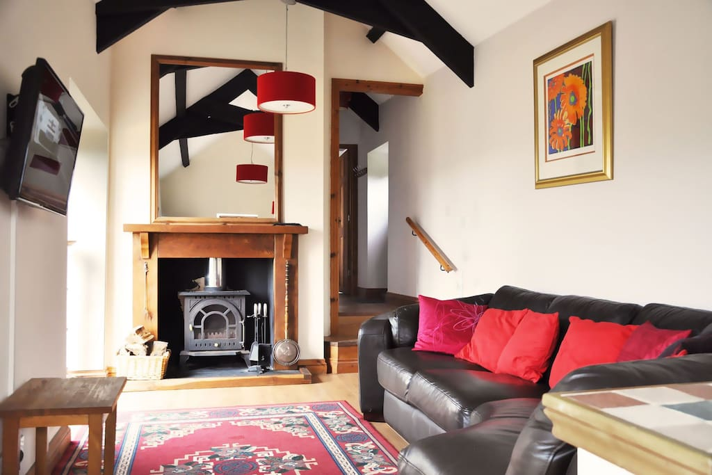 Ground floor: Open plan sitting room with high pitched ceiling & French doors