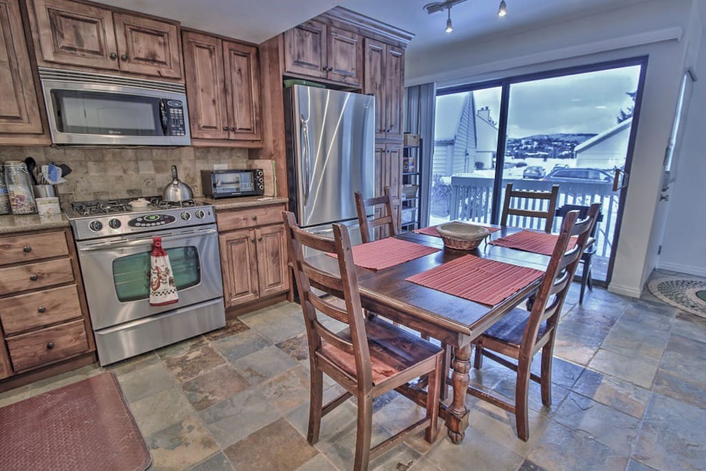 Kitchen with granite counters, stainless appliances, and dining area