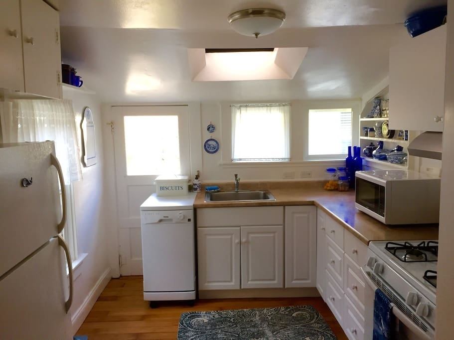 The kitchen is small, but functional with plenty of dishes and cookware.
