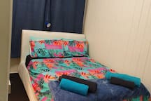 Double bed in bedroom with 2 pillows per guest bed has top and bottom sheets  we have put different coloured sheets to make it obvious, bath towel, bath sheet and a face cloth are provided for each guest, also block out curtains and ajustable lamp