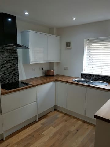 kitchen with dishwasher, washing machine, fridge, hob, built in microwave and oven