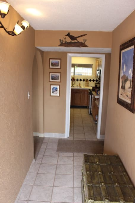 Foyer. To the right, 3 bedrooms and 2 bathrooms. To the left, living room. Straight ahead, the kitchen.