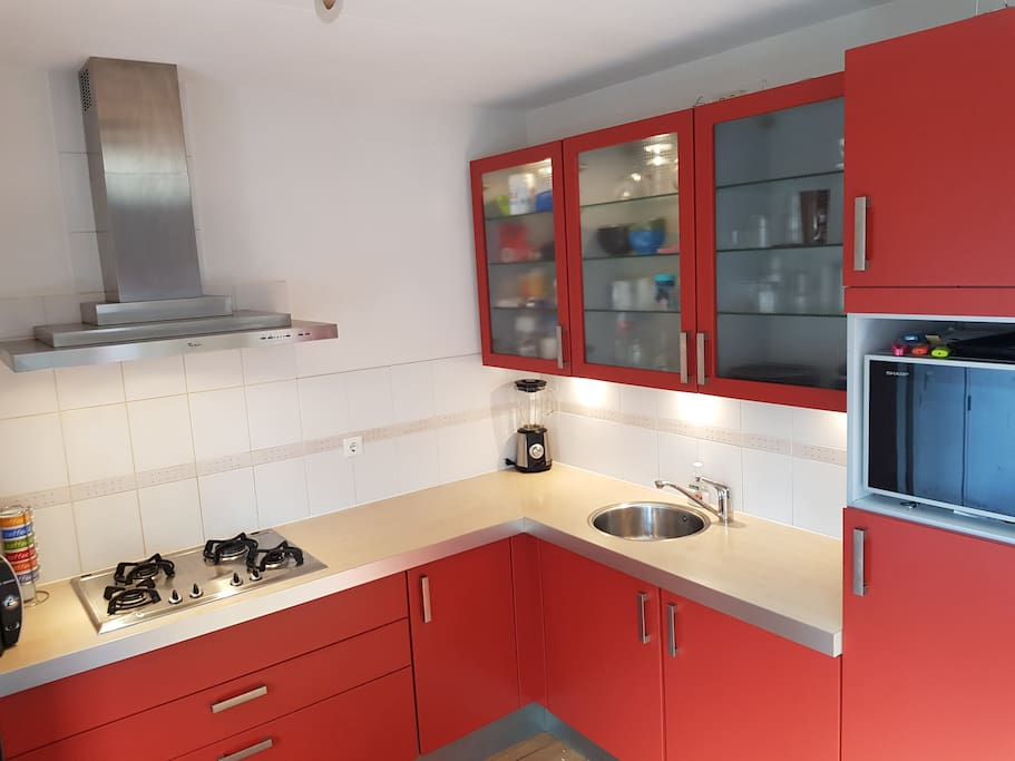 Kitchen with stove, combi microwave/oven, waterboiler, coffeemaker and various other items and appliances.