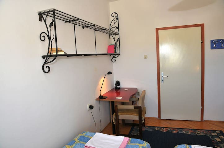 Shelves with some books, writing desk with drawers