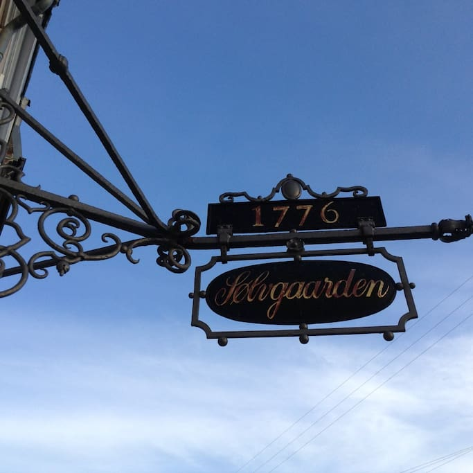Old street sign above the entrance door.