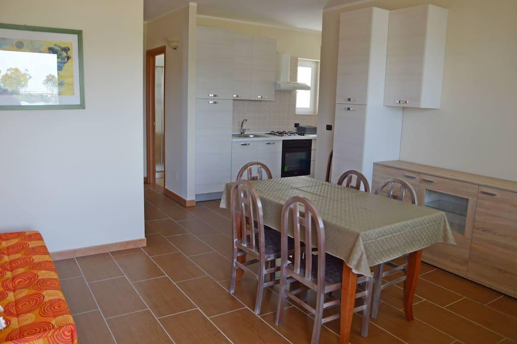 Angolo cottura + sala da pranzo + tv + divano letto
