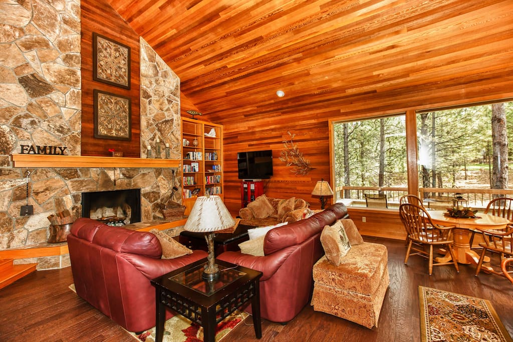 A wall of windows brings a pine and fir vista right into the airy living room.