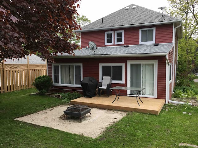 Back deck with chairs and table, natural gas bbq and small fire pit.