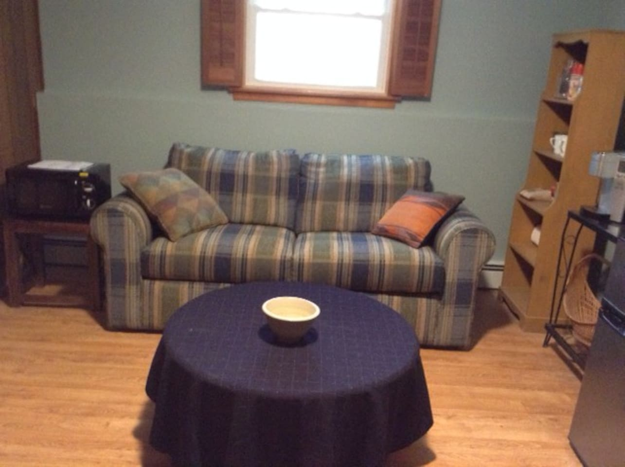 Sitting room containing fridge, coffee maker and microwave.