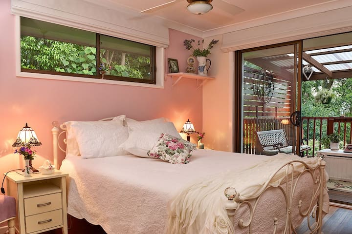 Main guest bedroom - beautiful  bedroom  with glass sliding door to spacious deck  which overlooks the tranquil gardens.