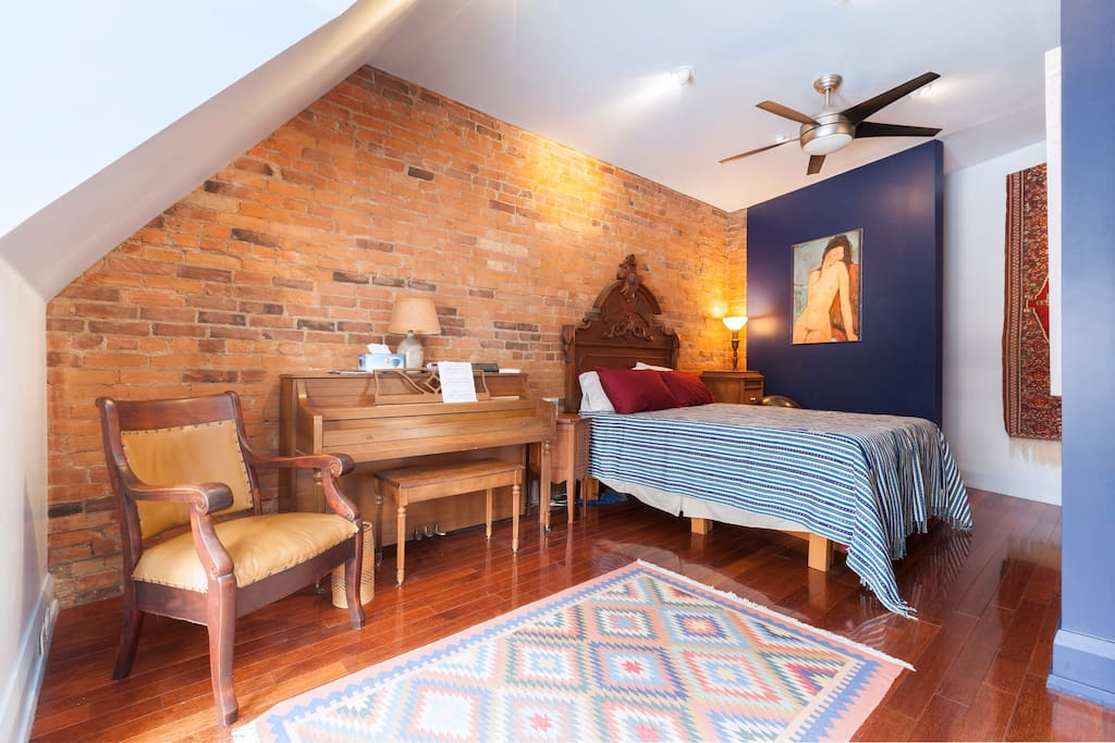 Master bedroom with gorgeous brick backdrop