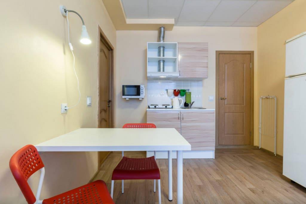 Кухня в полном составе: холодильник микроволновка, плита, чайник, вытяжка. В шкафах тарелки, кружки и разные кастрюли, сковородки и пр.
