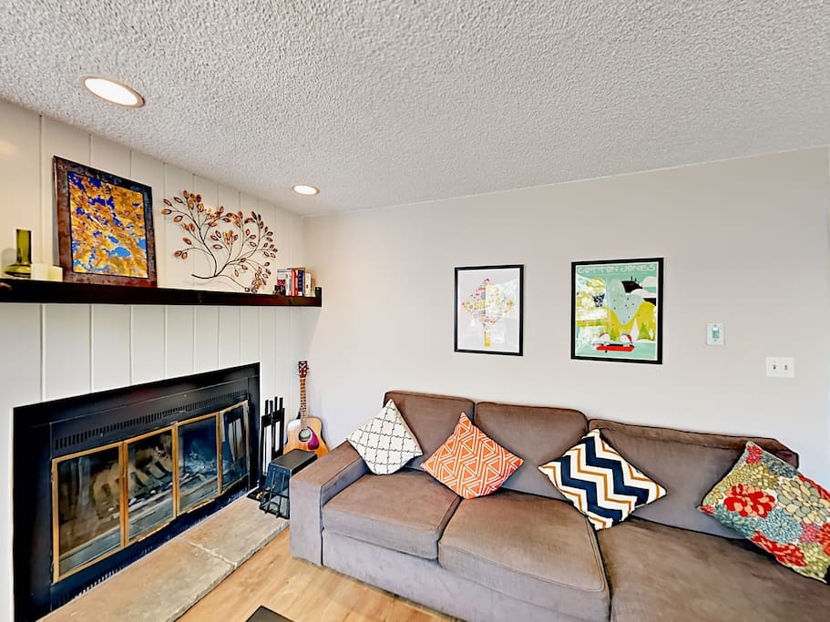 Welcome to Eagle-Vail! A wood-burning fireplace and colorful artwork accent the living room.