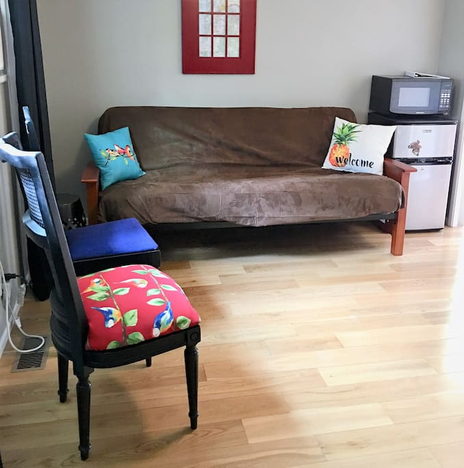 Living room with window air conditioner, queen futon with extra thick mattress.