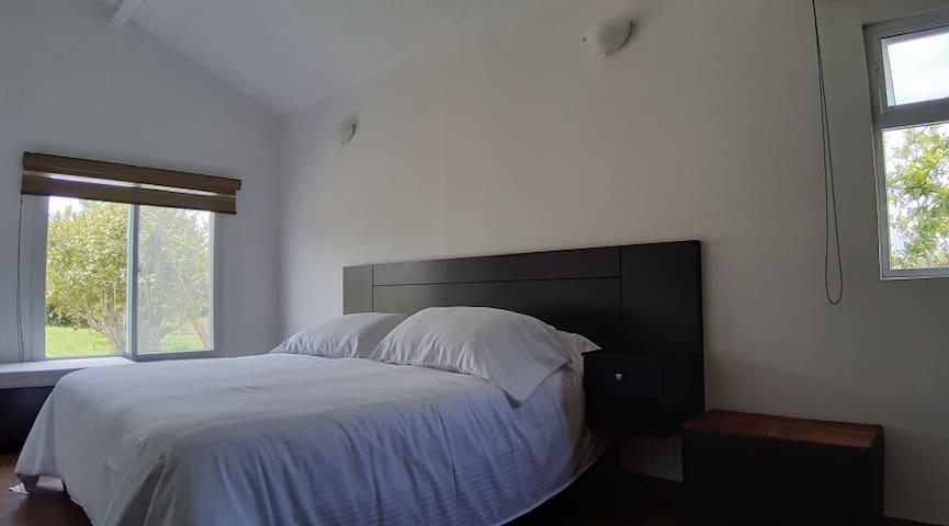 La recamara es amplia tiene cama king size y 2 buros laterales , ventanas con vista a la huerta, un pequeño sofá  (no se ve) para dormir niño pequeño.