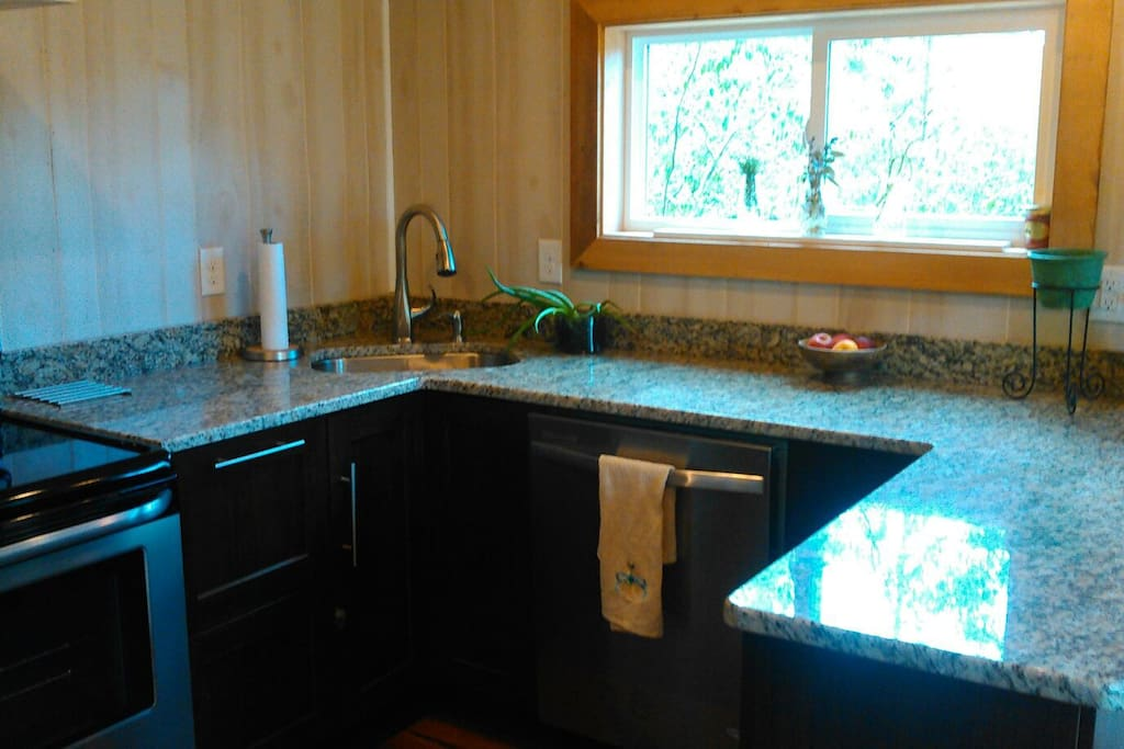 Kitchen has granite countertops, and all stainless steel appliances, range and hood, refrigerator, dishwasher, microwave.