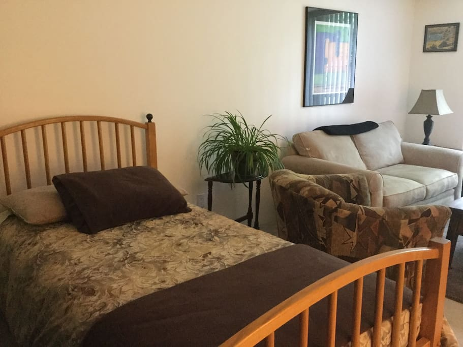 Single bed in common area with lounge area