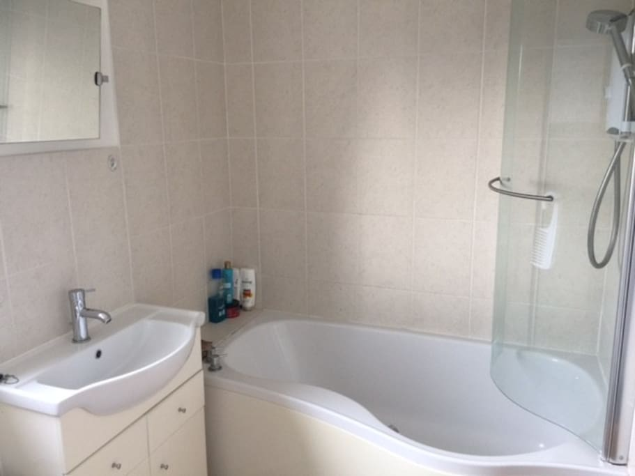 Shared bathroom with shower, toilet and sink. Clean and fresh.
