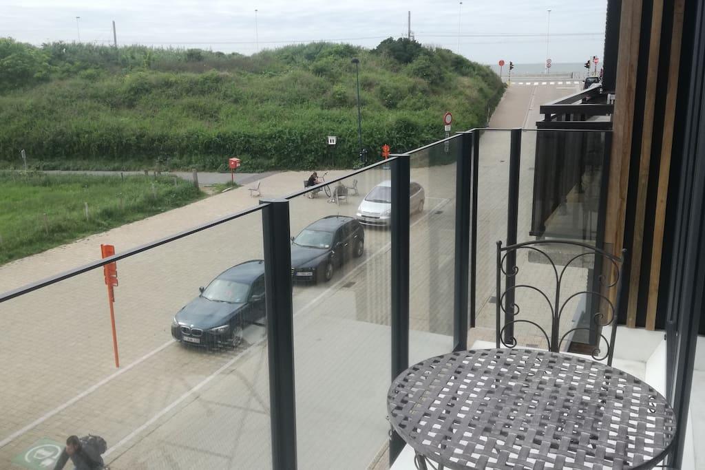 Zicht vanop terras naar de zee en de wandel- en fietsduinen