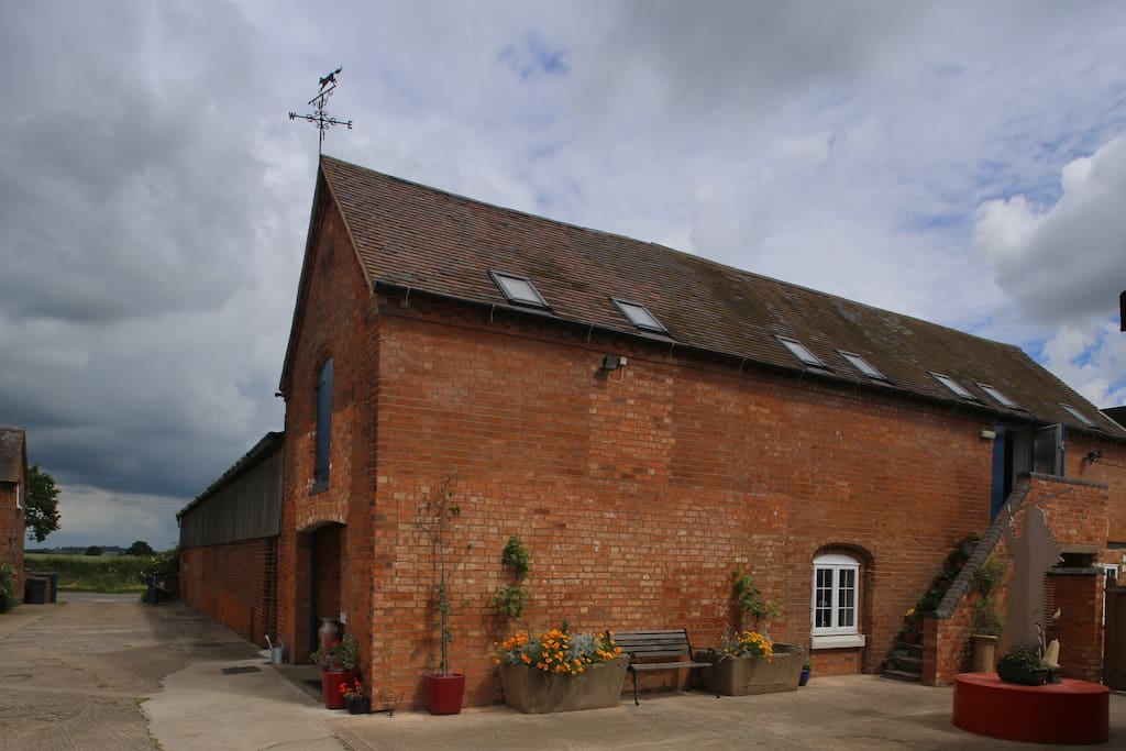 The outside of the barn with outdoor seating and parking.