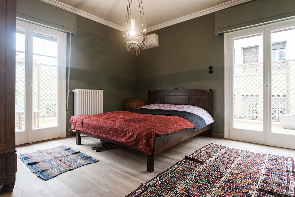 The large master bedroom features a traditional Greek wooden bed hand-crafted by an Athenian carpenter, a wooden cupboard from the 1920s, original demotic art, and a 19th century oil lamp