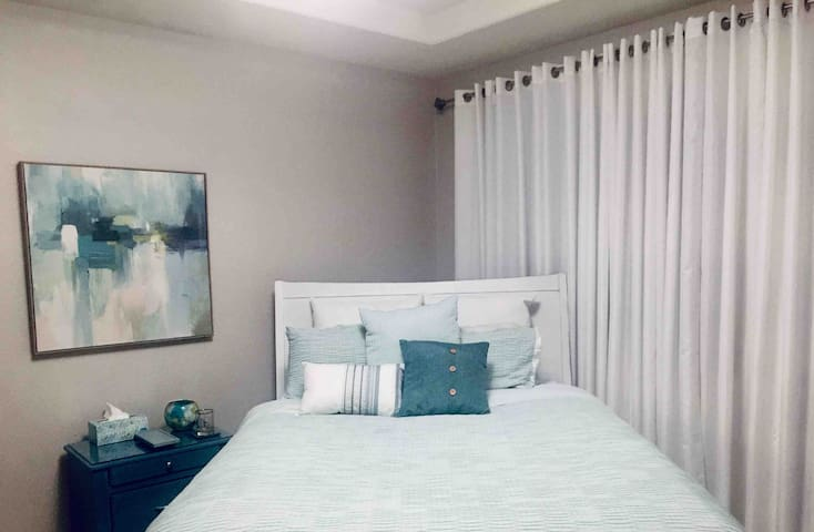 The Queen Size bed can be moved easily within the spacious bedroom, I like to change things up! Behind the curtains is a window and sliding glass door to the backyard patio.