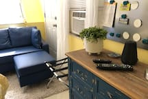 Guest bedroom with couch and stool. Door to outside with screen. The window air is no longer present because we have a central heat/air to the space 2019.     Speaker to play your tunes and charge your phones! Small chest of drawers.
