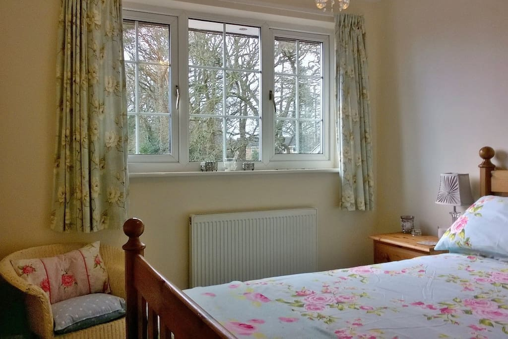 Freshly decorated double bedroom, with chair and bedside cabinets.