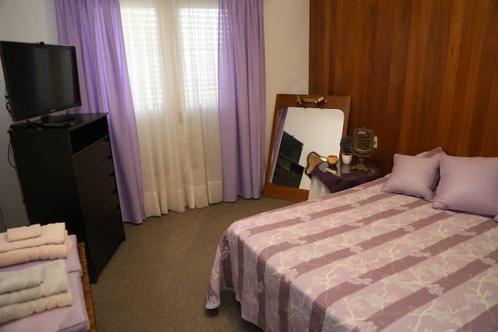 Habitación privada con cama matrimonial, luminosa con ventanal a la calle.