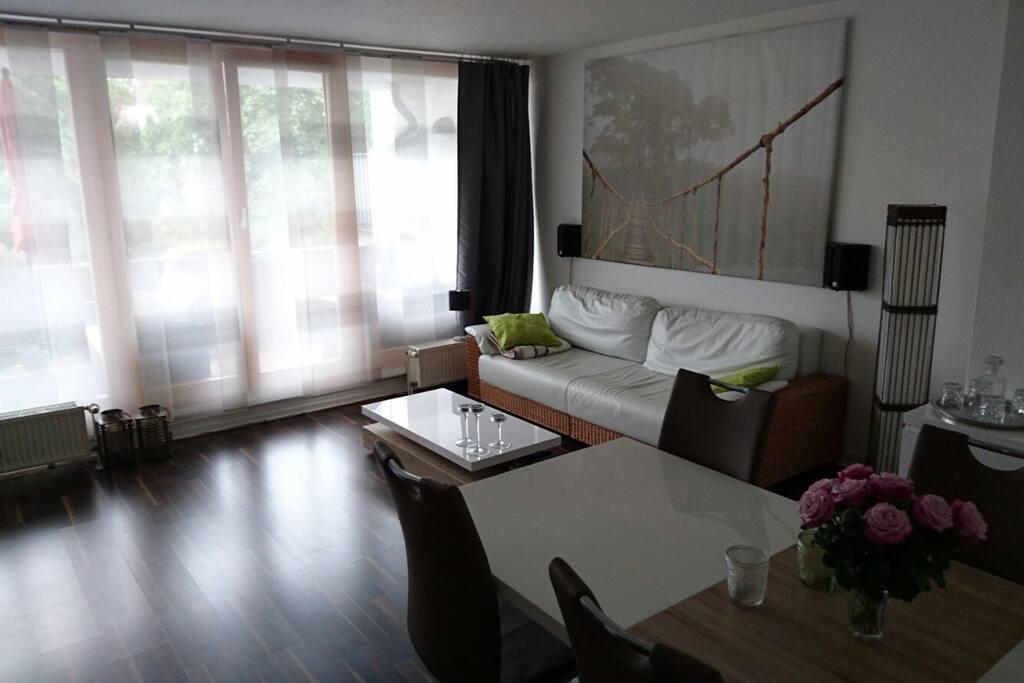 Wohnzimmer mit Sofa, TV, WLAN und großem Esstisch