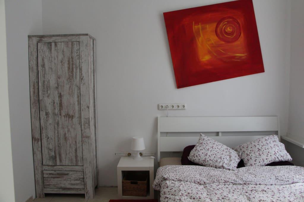 Schlafzimmer mit Schrank und Beistellstisch/Leuchte