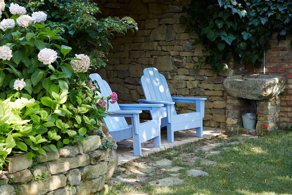 Adirondack chairs at the entrance of a stone walled room
