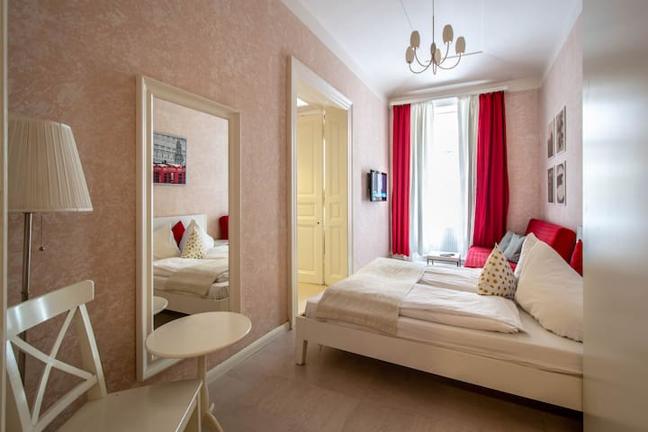 Other bedroom has convertible sofa, TV and mirror.