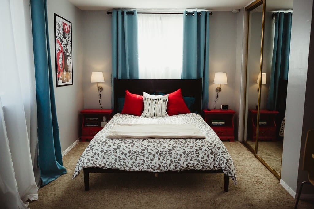 Bright and airy suite with comfortable queen-sized bed with custom lighting, artwork, and nightstands