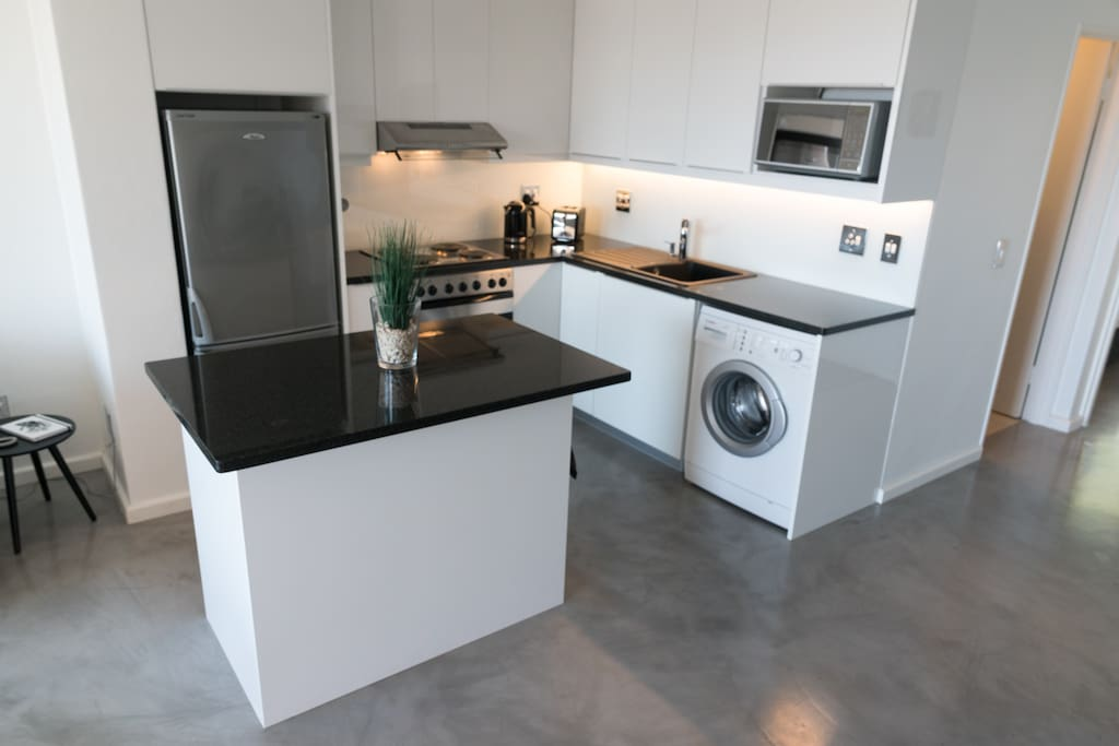 fully equipped kitchen with granite tops and washing machine