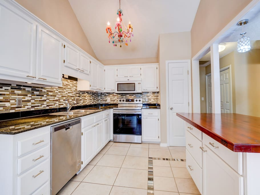 The kitchen features custom tile inlays, granite counters, stainless steel appliances, and an ample island with bar seating for 2.