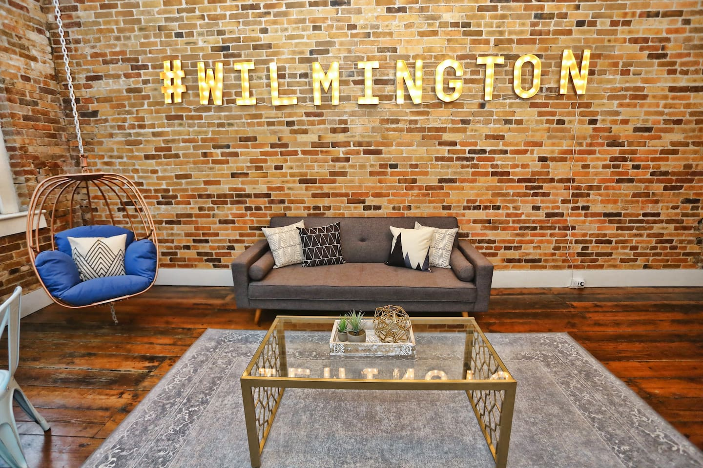 Living Room with swinging chair, light up #wilmington sign, and convertible mid-century sofa