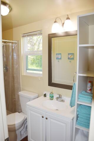 Bathroom with shower, fresh towels, shampoo, conditioner & soap.
