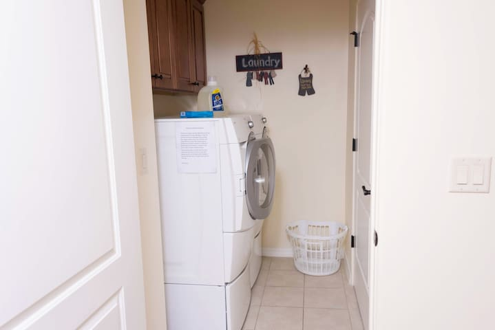 Laundry room has a front loading washer and dryer. Laundry closet has a iron and ironing board.