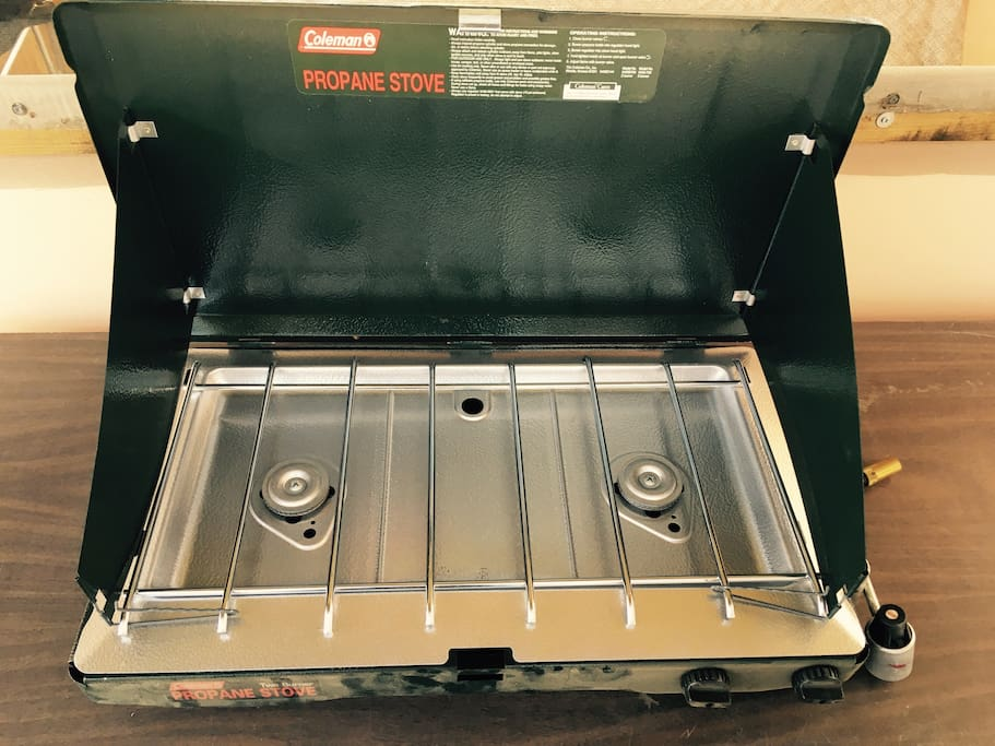 Coleman 2 burner propane camping stove on counter - 2 stools to sit and eat at counter