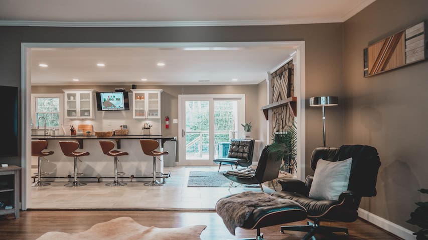 The living area merges seamlessly with the kitchen and den, centered around a twelve-foot island bar. This large surface acts as the dining table as well as a gathering space.