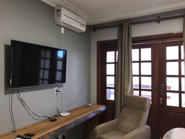 O quarto adaptado conta com uma televisão maior, uma poltrona e ar-condicionado, com acesso à varanda e com vista para o mar e par ao jardim.