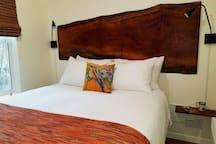 Handcrafted live edge headboard in main level bedroom, adjacent bath.