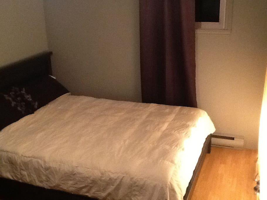 Un lit queen confortable avec couette en duvet