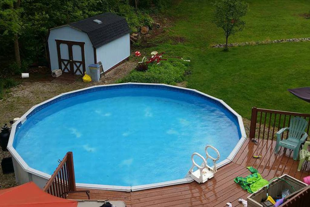 Large above ground swimming pool with deck and lounge chairs
