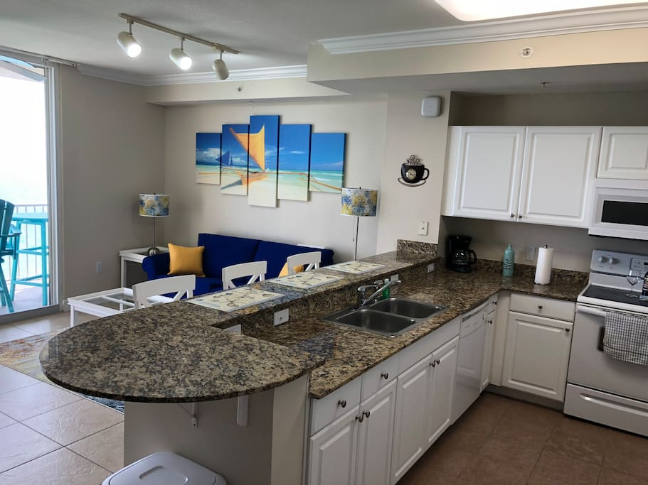 The kitchen, which is fully equipped with a refrigerator, microwave, oven, dishwasher, sink, toaster, coffee machine, various pots and pans, and all of the dinnerware you will need.